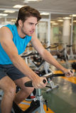 Homem apto focalizado na bicicleta da rotação foto de stock