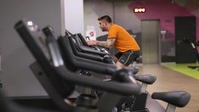 Homem apto que dá certo na bicicleta de exercício no gym com bokeh filme