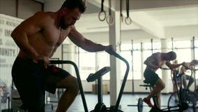 Homem apto que gira na bicicleta estacionária na classe do gym vídeos de arquivo
