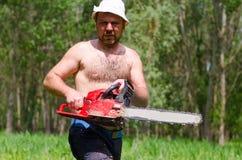 Homem apto que leva uma serra de cadeia na floresta Imagens de Stock