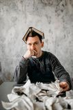 Homem arrepiante com o livro na cabeça contra folhas rasgadas Foto de Stock