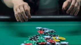 Homem arriscado que aposta todas as microplaquetas dentro ao jogar o pôquer no casino, apego do jogo video estoque