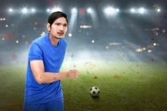 Homem asiático atrativo do jogador de futebol que corre com bola Foto de Stock