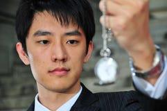 Homem asiático com relógio de bolso 3 imagens de stock
