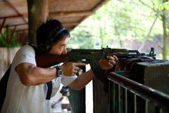 Homem asiático com um rifle na posição pronta Imagens de Stock