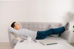 Homem asiático considerável novo que dorme no sofá imagem de stock royalty free