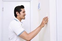 Homem asiático considerável que desliga a luz com o interruptor da parede fotografia de stock royalty free