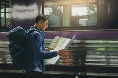 Homem asiático da vista traseira que guarda o papel do mapa e que olha o roteador com pl imagens de stock
