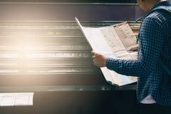 Homem asiático da vista traseira que guarda o papel do mapa e que olha o roteador com plano para o curso fotos de stock royalty free
