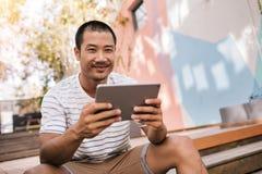 Homem asiático de sorriso que senta-se em escadas fora de usar uma tabuleta Fotos de Stock Royalty Free