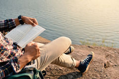 Homem asiático feliz do moderno que lê um livro no fundo da natureza fotos de stock