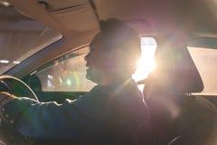 Homem asiático feliz que conduz um carro com raio do sol fotografia de stock royalty free