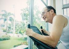 Homem asiático idoso que corre em uma escada rolante Fotografia de Stock