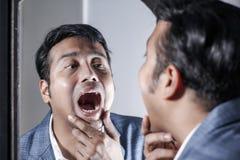 Homem asiático no terno que ocupa de sua aparência na frente de uma beleza do espelho que denomina o estilo de vida imagem de stock royalty free