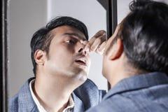 Homem asiático no terno que ocupa de sua aparência na frente de uma beleza do espelho que denomina o estilo de vida fotos de stock royalty free