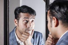 Homem asiático no terno que ocupa de sua aparência na frente de uma beleza do espelho que denomina o estilo de vida imagem de stock