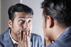 Homem asiático no terno que ocupa de sua aparência na frente de uma beleza do espelho que denomina o estilo de vida fotografia de stock royalty free