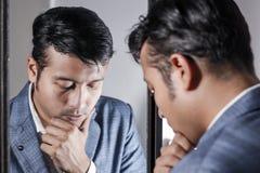 Homem asiático no terno que ocupa de sua aparência na frente de uma beleza do espelho que denomina o estilo de vida foto de stock