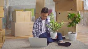 Homem asiático novo após mover-se para um apartamento novo que senta-se em um portátil no assoalho filme