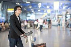 Homem asiático novo com bagagem no terminal de aeroporto Fotografia de Stock
