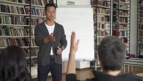 Homem asiático novo com um flipchart que dá uma leitura na biblioteca video estoque