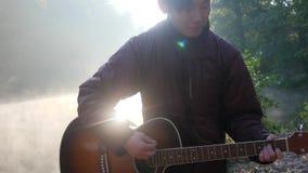 Homem asiático novo considerável que joga a guitarra na costa do rio da floresta no nascer do sol Névoa enevoada do alvorecer no  video estoque