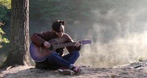 Homem asiático novo considerável que joga a guitarra na costa do rio da floresta no nascer do sol Névoa enevoada do alvorecer no  vídeos de arquivo