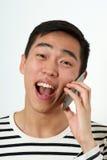 Homem asiático novo de riso que usa um smartphone imagem de stock royalty free