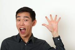 Homem asiático novo de sorriso que acena sua palma e vista da câmera imagem de stock royalty free