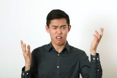 Homem asiático novo desagradado que gesticula com duas mãos foto de stock