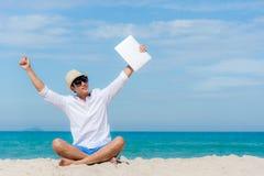 Homem asiático novo do estilo de vida que relaxa após o trabalho no portátil ao sentar-se na praia bonita, trabalho autônomo no f fotografia de stock royalty free