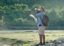 Homem asiático novo do turista com água potável da trouxa imagens de stock royalty free
