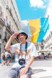 Homem asiático novo do turista que senta-se fora com uma câmera imagem de stock royalty free