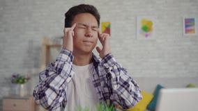 Homem asiático novo em uma camisa com uma dor de cabeça que senta-se no portátil vídeos de arquivo