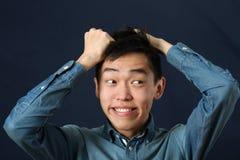 Homem asiático novo engraçado que faz a cara Fotografia de Stock Royalty Free