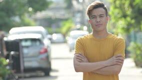 Homem asiático novo feliz que sorri com os braços cruzados fora filme