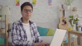 Homem asiático novo na pessoa deficiente dos vidros à moda em uma cadeira de rodas com trabalho remotamente do portátil na sala d filme