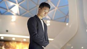 Homem asiático novo no revestimento e na camisa que procuram pela informação na exposição interativa vídeos de arquivo