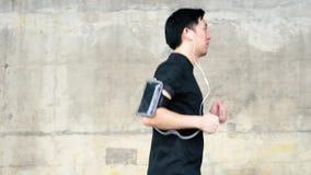 Homem asiático novo que corre na cidade e no fones de ouvido vestindo vídeos de arquivo