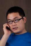 Homem asiático novo que fala no telefone Foto de Stock Royalty Free