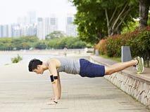 Homem asiático novo que faz flexões de braço no parque Fotos de Stock Royalty Free
