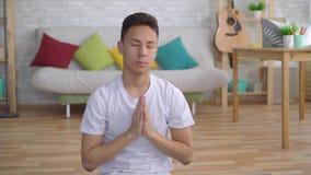 Homem asiático novo que faz a ioga que senta-se no fim da esteira acima video estoque