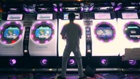 Homem asiático novo que joga Arcade Machine Drum Music Game e que empurra o controlador brilhante Buttons 4K Zona do jogo em MBK video estoque