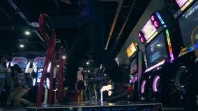 Homem asiático novo que joga o jogo da revolução da dança e que faz truques da dança em Arcade Machine Pad na compra da zona MBK  vídeos de arquivo