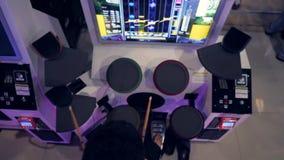 Homem asiático novo que joga o jogo dos cilindros na música Arcade Machine Pads no shopping da zona MBK do jogo 4K Banguecoque, T video estoque
