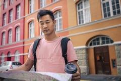 Homem asiático novo que lê um mapa ao explorar a cidade fotos de stock royalty free