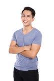 Homem asiático novo que levanta no fundo branco, braços cruzados fotografia de stock royalty free