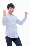 Homem asiático novo que mostra o punho e o sinal feliz. Imagens de Stock