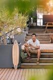 Homem asiático novo que relaxa em etapas fora das mensagens de texto da leitura Foto de Stock Royalty Free