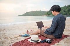 Homem asiático novo que trabalha com o portátil na praia fotos de stock